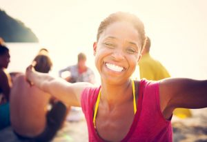 black woman on the beach with friends smiling and spreading her arms with joy while smiling at the camera
